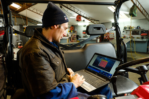 Mechanic using a laptop to diagnose at Winton Motorcycles